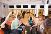 Friends Cheering Woman Bowling in Club — Stock Photo