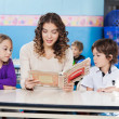 Teacher Reading Book While Children Listening To Her — Foto Stock