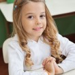 Stock Photo: Girl Sitting With Hands Clasped In Classroom