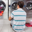 Man Sitting In Front Of Washing Machines — Stock Photo #31184949