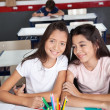 Schoolgirl Sitting With Classmate At Desk In Classroom — Stock Photo
