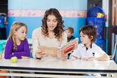 Profesor de lectura mientras los niños escuchando — Foto de Stock