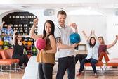 Enthousiast man en vrouw met bowling ballen in club — Stockfoto