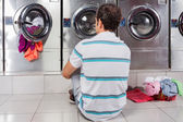 Man Sitting In Front Of Washing Machines — Stock Photo