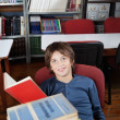 Schoolboy Sitting With Stacked Books At Table — Stock Photo #31499163