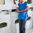 Confident Female Helper Standing By Dryers — Stock Photo