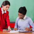 Schoolgirl Asking Question To Female Teacher At Desk — Stock Photo #31506225
