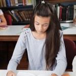 Студентка чтения книги в таблице в библиотеке — Стоковое фото