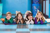 Kinderen liggen in een rij op verdieping in klas — Stockfoto