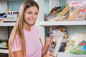 Woman Holding Food Packet In Grocery Store — Stock Photo