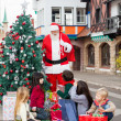 Children With Gifts Looking At Santa Claus — Stock Photo #31634171
