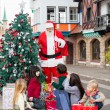 Stock Photo: Children With Gifts Looking At Santa Claus