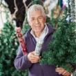 Man Holding At Christmas Tree And Baubles In Store — Stock Photo
