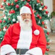 Santa Claus Sitting Against Christmas Tree — Stock Photo