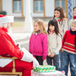Stock Photo: Santa Claus Looking At Children Standing In A Queue