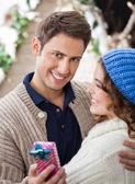 Szczęśliwy człowiek Ogarnięcie kobieta w sklepie Boże Narodzenie — Zdjęcie stockowe
