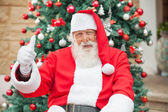 Santa Claus Gesturing Thumbsup Against Christmas Tree — Stock Photo
