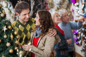 Young Couple In Christmas Store With Parents In Background — Stock Photo