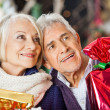 Couple With Christmas Presents In Store — Stock Photo