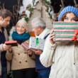 Thoughtful Woman Holding Christmas Present With Family In Backgr — Stock Photo #31646897
