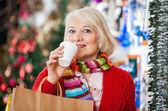 Mulher com sacos de compras, beber café na loja de natal — Foto Stock