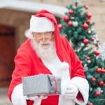 Santa Claus Giving Christmas Present — Stock Photo #31652681