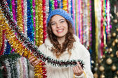 Young Woman Choosing Tinsels At Store — Stock Photo