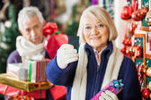 Kobieta trzyma karty kredytowej w sklepie Boże Narodzenie — Zdjęcie stockowe