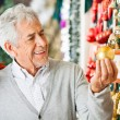 Man Buying Christmas Baubles At Store — Stock Photo