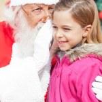 Santa Claus Whispering In Girl's Ear — Stock Photo #31727739