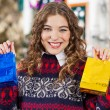 Happy Woman Holding Small Shopping Bags In Store — Stock Photo