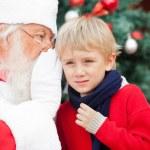 Santa Claus Whispering In Boy's Ear — Stock Photo #31728691