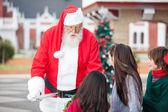 Santa Claus Offering Cookies To Children — Stock Photo