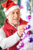 Dueño masculino decorar el árbol de navidad en tienda — Foto de Stock