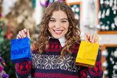 Heureuse femme tenant des petits sacs à provisions en magasin — Photo