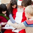 Santa Claus With Children Pointing At Book — Stock Photo #31732771