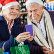 Senior Couple Using Mobilephone At Christmas Store — Lizenzfreies Foto