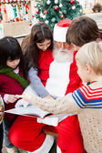 Santa Claus With Children Pointing At Book — Stok fotoğraf