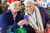 Senior Couple Using Mobilephone At Christmas Store — Stock Photo
