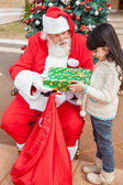Girl Receiving Present Against Christmas Tree — Stock Photo