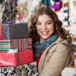 Woman Carrying Stacked Christmas Presents In Store — Stock Photo