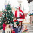 Stock Photo: Santa Claus And Children With Gifts By Christmas Tree