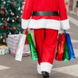 Santa Claus With Shopping Bags Walking In Courtyard — Stock Photo