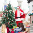 Stock Photo: Santa Claus With Children Opening Presents By Christmas Tree