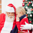 Boy Whispering In Santa Claus's Ear — Stock Photo #31742847