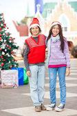 Przyjaciele sobie santa hat stojący na dziedzińcu — Zdjęcie stockowe