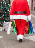 Santa claus mit einkaufstüten, die zu fuß in hof — Stockfoto