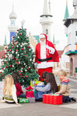Santa Claus With Children Opening Presents By Christmas Tree — Stock Photo