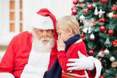 Boy Whispering In Santa Claus's Ear — Stock Photo