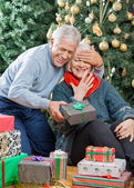 Man Surprising Senior Woman With Christmas Gifts In Store — Stock Photo